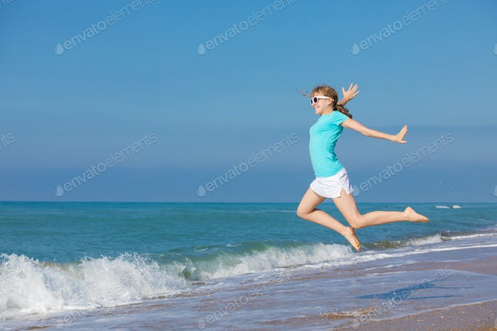 teen girl jumping on the beach at blue sea shore in summer vacat