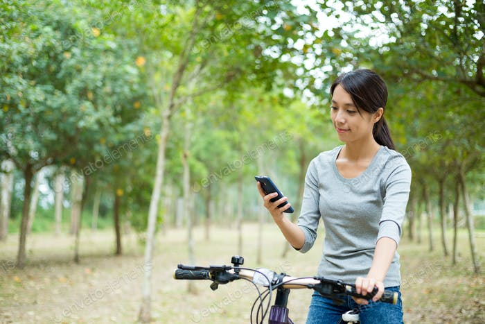 Woman checking the GPS on mobile phone when cycling