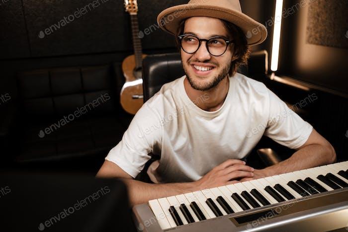 Junge attraktive stilvolle Musiker arbeiten glücklich im modernen Tonaufnahmestudio