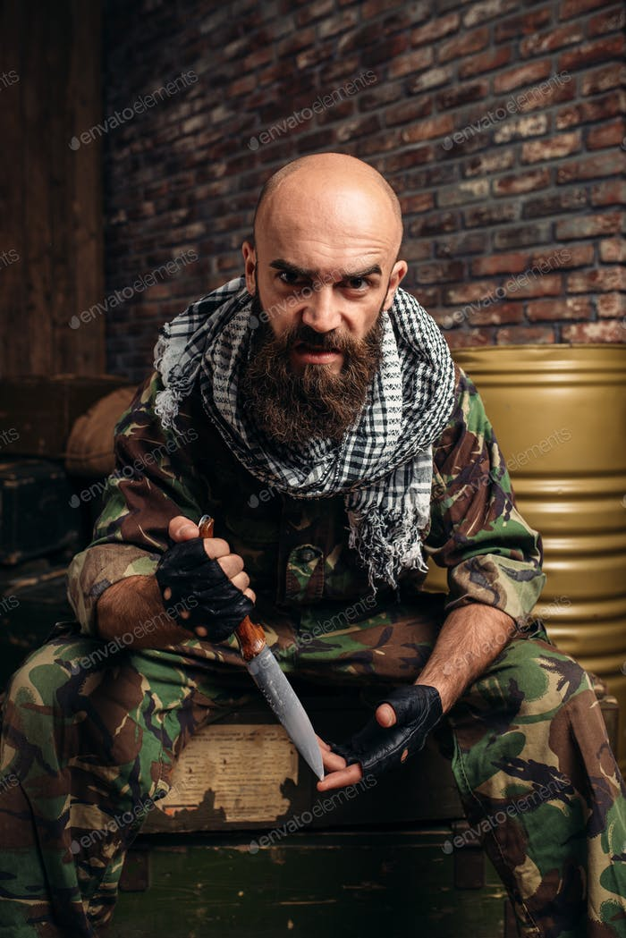 Terrorist with knife sits on boxes of ammunition