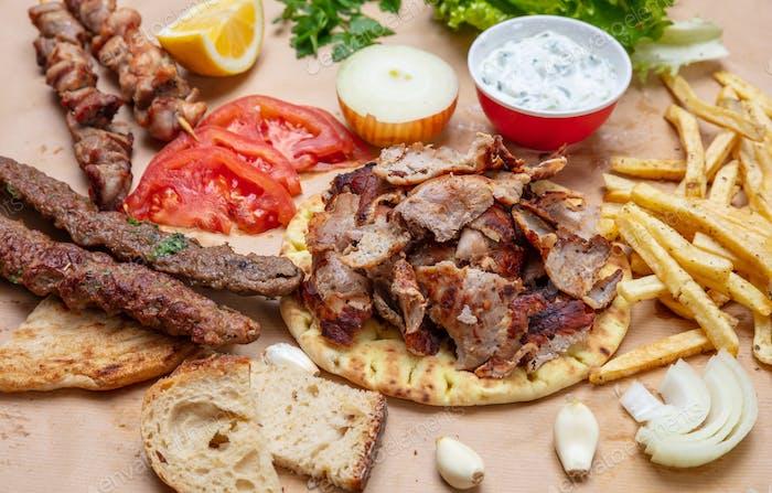 Traditional turkish, greek meat food. Shawarma, gyros, kebab, souvlaki and tzatziki on pita bread