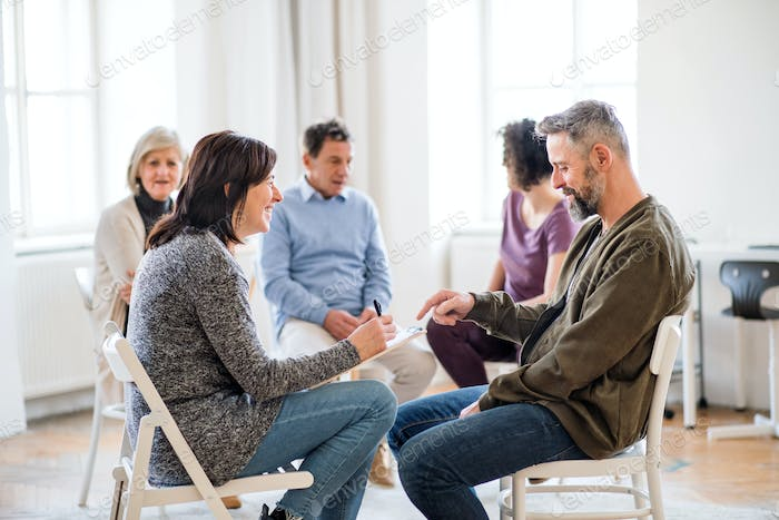 Senior counselor with clipboard talking to a man during group therapy.