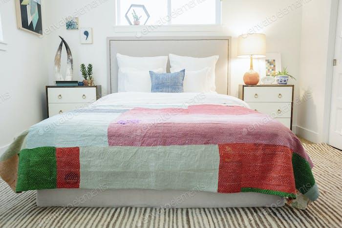Ein Schlafzimmer in einer Wohnung mit einem Doppelbett und einem antiken gemusterten Bett im Retro-Look