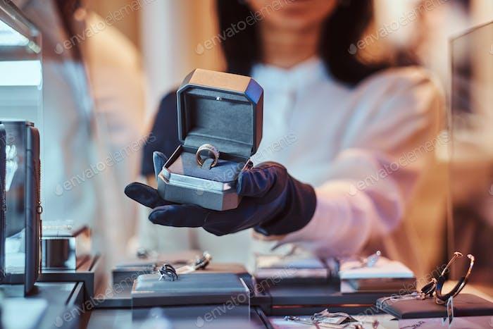 Frau Assistentin zeigt den exklusiven Goldring im Juwelier
