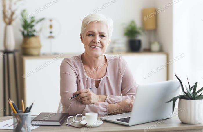 Smiling granny working with laptop at home