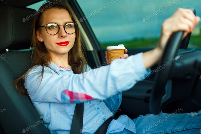 Woman with coffee to go driving her car