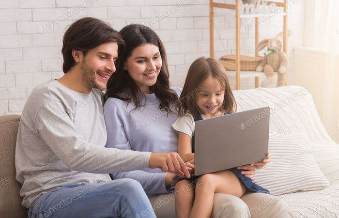 Happy young family with daughter using laptop together at home