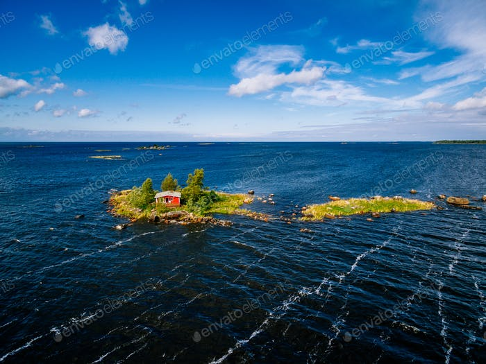 A small red cottage on an island in the blue sea on a summer day. Finland. View from above.