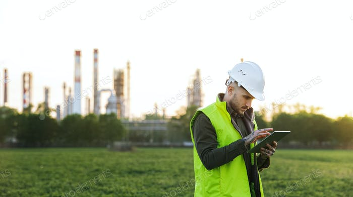 Young engineer with tablet standing outdoors by oil refinery. Copy space