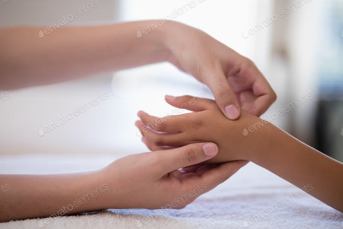 Close-up of female therapist examining hand on white towel