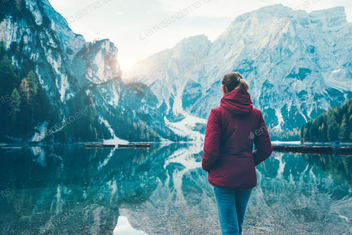 Woman in red jacket standing on the coast of Braies lake