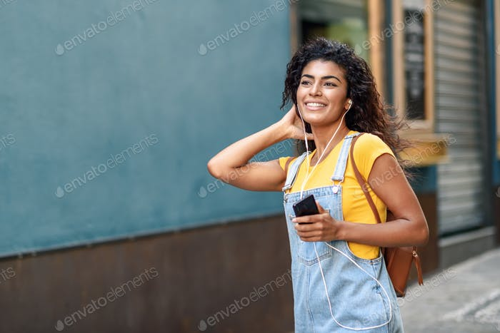 Attractive African woman listening to music with earphones