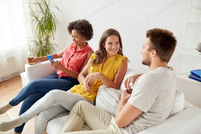 group of happy friends with beer talking at home