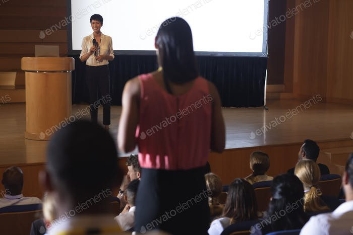 Beautiful businesswoman discussing while woman from the audience asking query