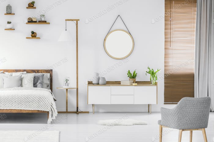 Scandinavian style white room interior with round mirror on the