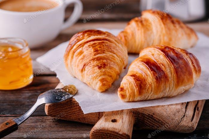 Hausgemachte gebackene Croissants mit Marmelade und Kaffee auf rustikalem Holzhintergrund