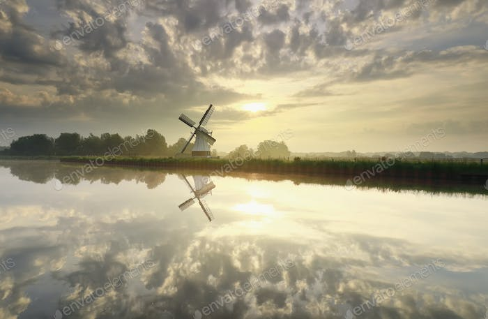 sunrise over white Dutch windmill and river