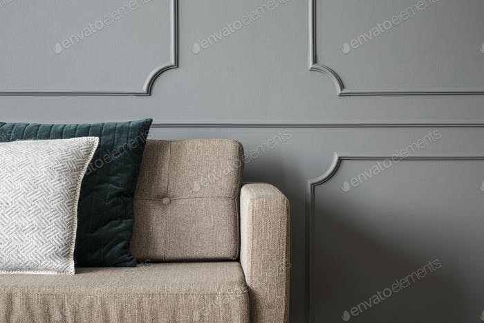 Close-up of pillows on beige sofa against grey wall with molding