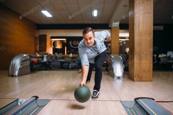 Male bowler throws ball on lane, front view