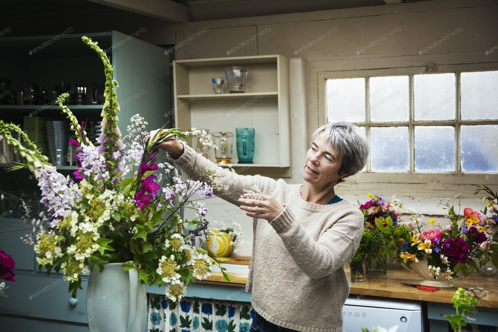 A Florist Working On A Tall Vase Arrangement Of Flowers Photo By Mint Images On Envato Elements