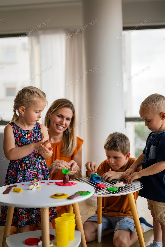 Family, children, education, happiness concept. Mother teaches preschooler kids to do craft items