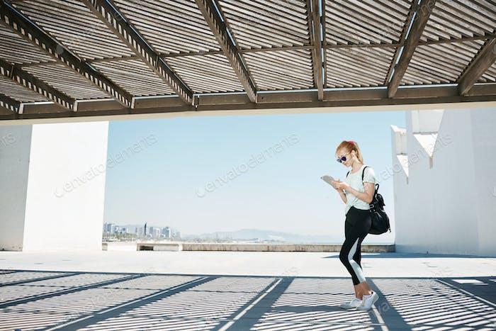 Fit азиатская девушка в спортивной одежде, слушая музыку с наушниками