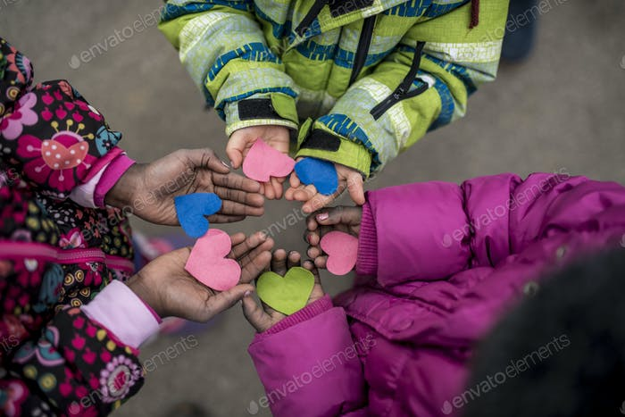 Children holding hearts in hands