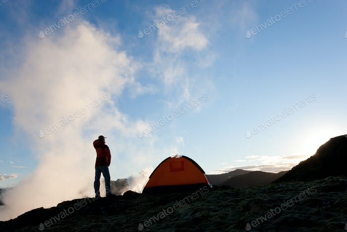 Woman standing by tent at sunrise, Iceland