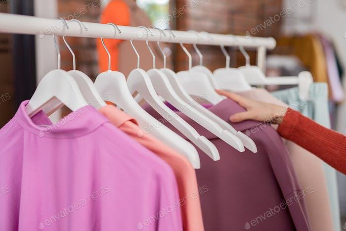 Weibliche Hand mit einem Kleiderbügel
