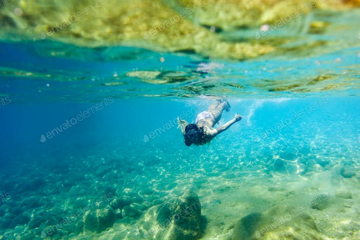 Young woman snorkeling and diving in tropical sea