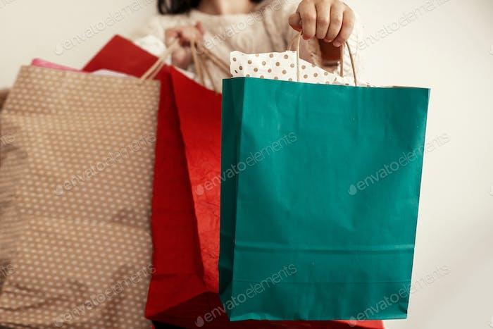 Happy Girl in Pullover hält rote und grüne Papier-Einkaufstaschen