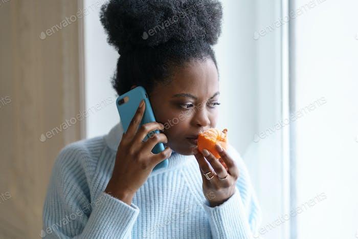 Sick afro woman trying to sense smell of half fresh tangerine orange talking on phone. Covid-19