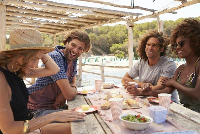 Mixed race couple lying on the beach holding hands, Ibiza