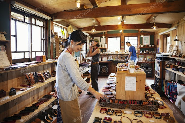 Two Japanese women and man standing in a leather shop.