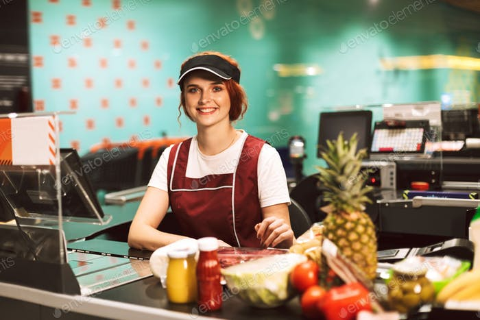 Young beautiful cashier in uniform happily looking in camera whi