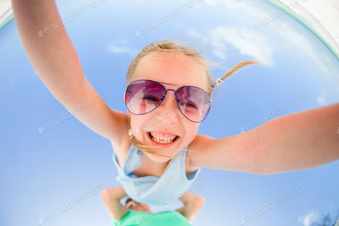 Little girl outdoors during summer vacation have fun with father. Portrait of a kid upside down on a