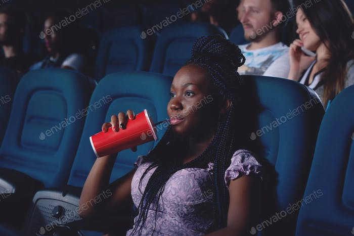 African girl drinking cola and watching movie