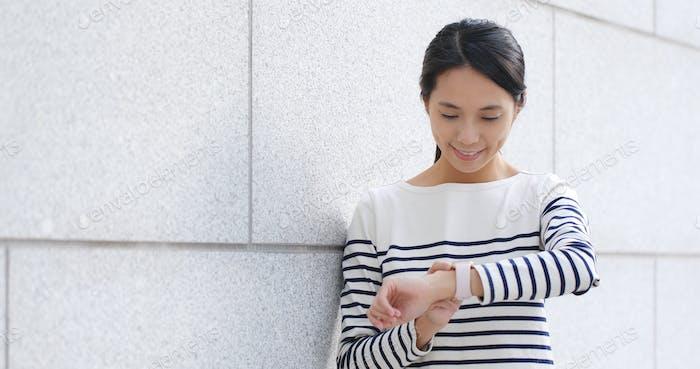 Mujer chequeando horario en reloj inteligente