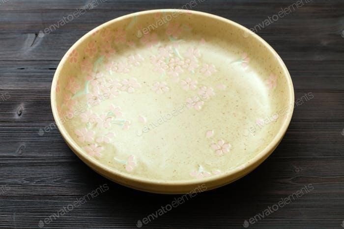 grüner Teller auf dunkelbraunem Tisch