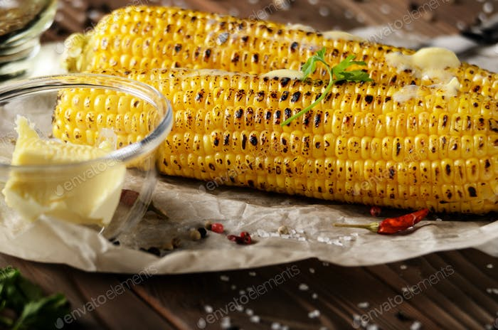 Kitchen table with grilled sweet corn cob under melting butter a