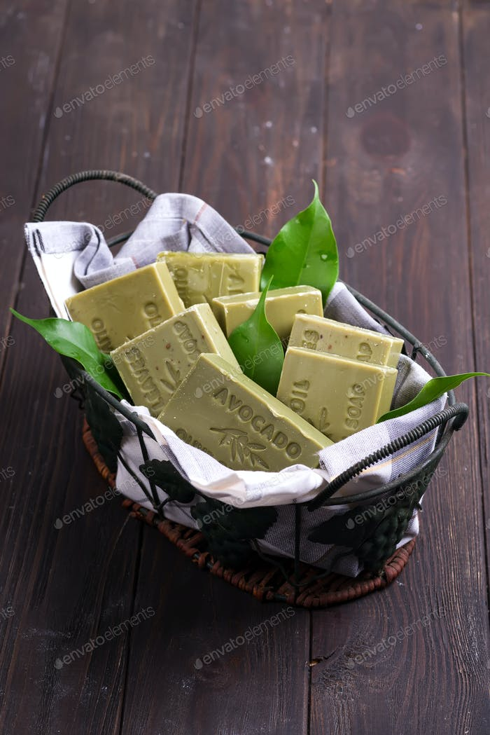 Bars of green natural olive oil soaps with green leaves in a basket on dark wooden background, top