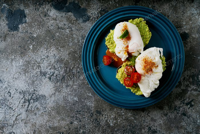 Avocado toasts with poached egg on the plate