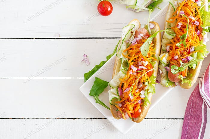 Hot dog with  cucumber, carrot, tomato and lettuce on wooden background. Fast food menu. Top view