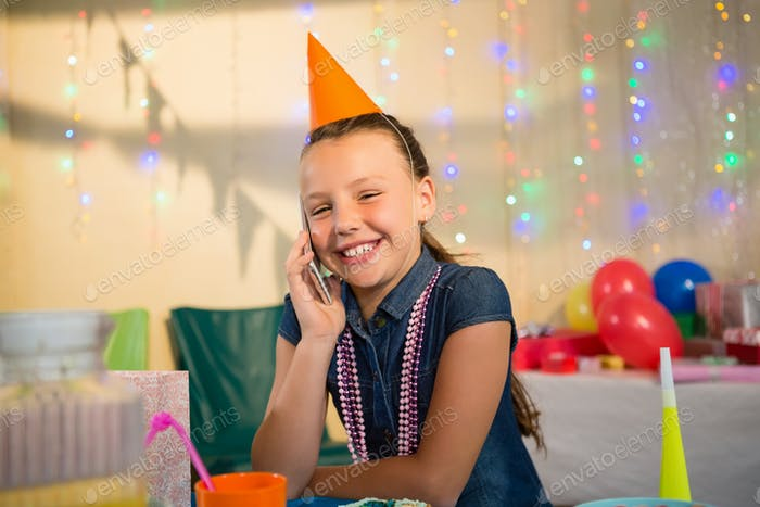 Girl talking on mobile phone during birthday party