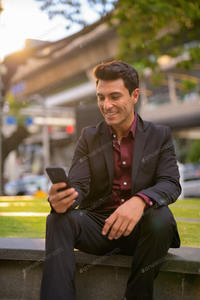 Happy handsome Hispanic businessman using phone and sitting with nature in city