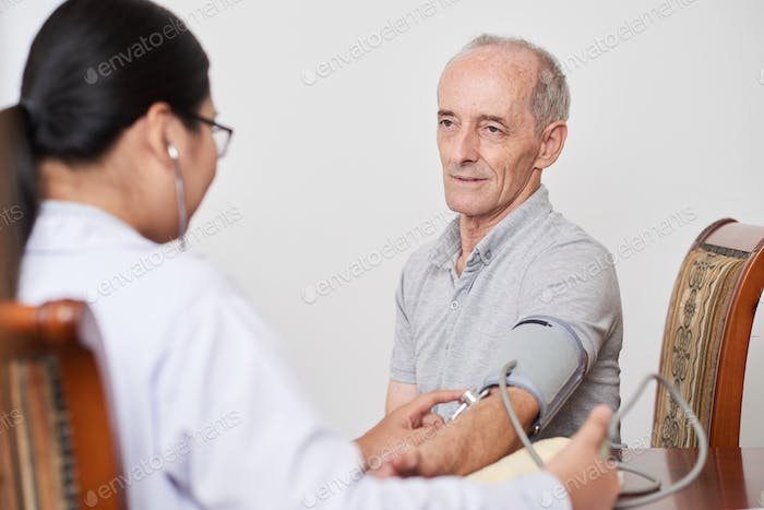 Senior patient with doctor at home