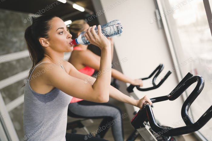 Women cycling in gym during fitness class