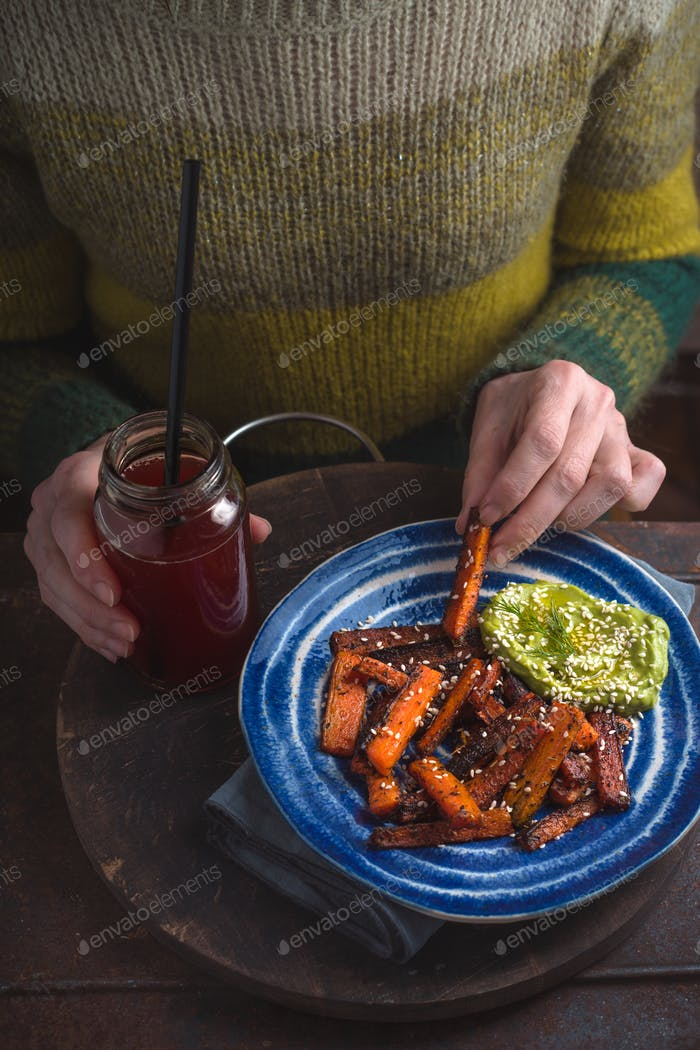 Woman in a green sweater eating fried carrot copy space