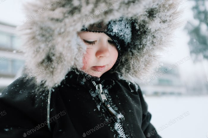 Young boy playing in snow with snowy hood