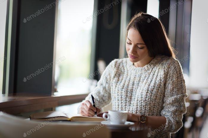 Schöne Frau sitzt im Restaurant und Schreiben